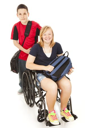 Teen boy pushes his disabled friend in her wheelchair on the way to school.   Stockfoto