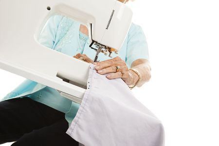 Closeup of a senior womans hands as she uses a sewing machine.   photo
