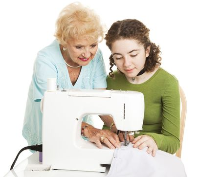 Grandmother teaching her teen granddaughter to use a sewing machine.  Isolated on white.  photo