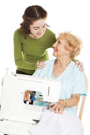 Teen girl watching her grandmother sew on a sewing machine.  Isolated. photo