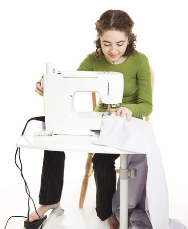 pedaling: Teen girl using a sewing machine.  Full body isolated on white. Stock Photo
