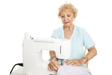 Senior woman making curtains on a sewing machine.  Isolated on white. photo