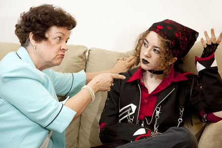 troubled teen: Angry mother pointing the finger at her rebellious teenage daughter.  Focus on the mom.