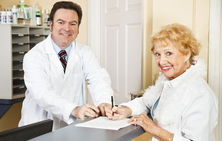 Doctor helps senior patient with her medical forms.   photo