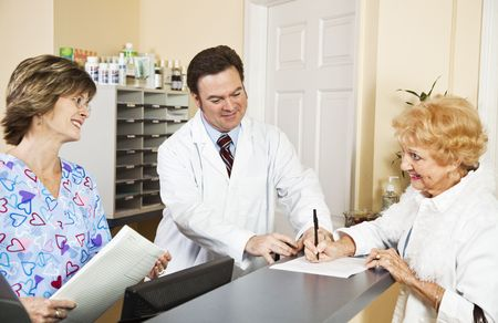 Doctor and nurse greating a new patient as she signs in.  Focus on doctor. photo