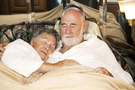 Senior couple sound asleep in the bed of their motor home.