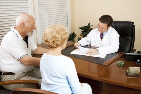 medical history: Senior couple with the doctor, going over medical history.   Stock Photo