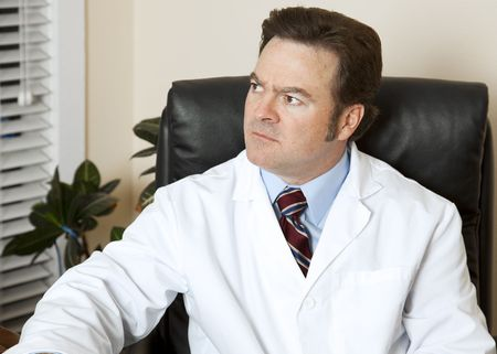 Doctor in his office, worried about a patient. Stock Photo - 6589928
