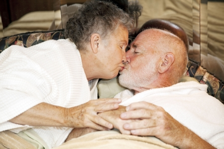 Romantic senior couple in bed kissing goodnight.   Stock Photo - 6589935