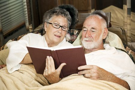 glass bed: Senior couple reading together in the bed of their motor home.