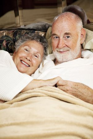 snuggling: Happy senior couple snuggling in bed.  Vertical view.