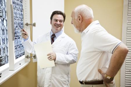 orthopaedics: Doctor o quiropr�ctico explicando los resultados de una TC de la columna vertebral a su paciente sufriendo con dolor de espalda bajo.   Foto de archivo