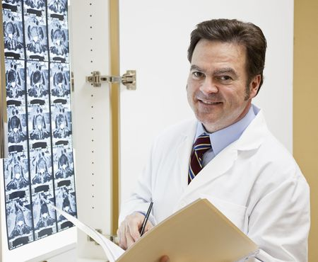 ct: Chiropractic doctor reads a patients chart and examines a CT scan of their spine.