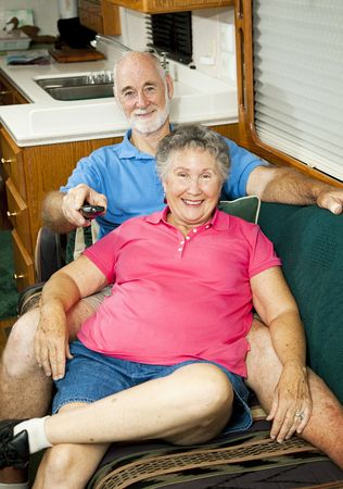 couple on couch: Senior couple watches TV in the cabin of their motor home.   Stock Photo