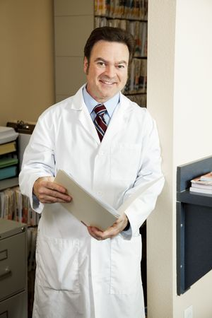 Handsome doctor in his office going over a patients medical history.   photo