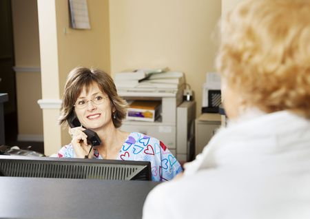 Receptionist in a doctors office greets a patient.