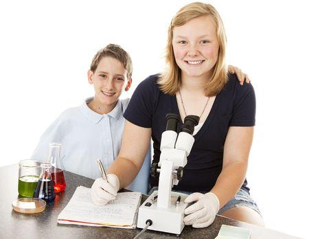 Ni�os en la escuela, haciendo experimentos cient�ficos y examinar los resultados bajo microscopio.  Fondo blanco. Foto de archivo - 6676105