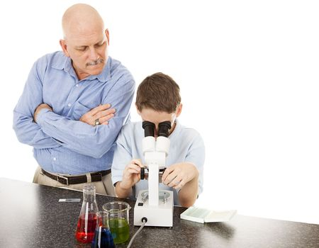 Science teacher watches as a student examines slides under the microscope.  White background.   Stock Photo - 6676110