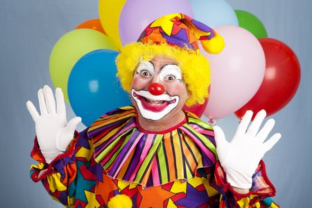 Happy birthday clown with balloons, holding his hands in a surprised gesture.   photo