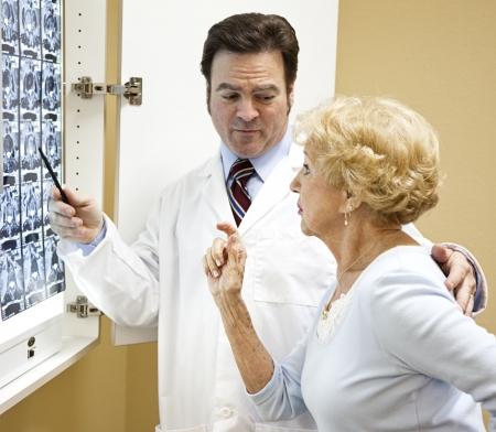 orthopaedics: Mujer Senior con su m�dico, mirando los resultados de su an�lisis de gato.   Foto de archivo