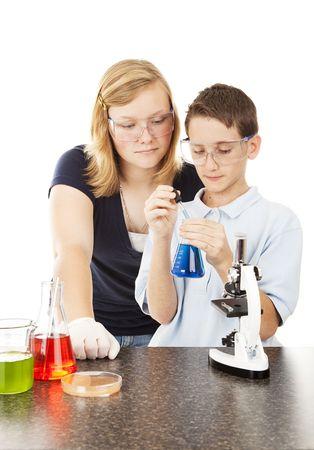 Ni�os haciendo experimentos de la ciencia en la escuela.  Aislados en blanco.  Foto de archivo - 6713389
