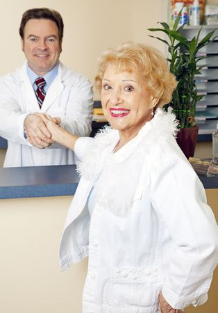 Beautiful, satisfied senior patient shaking hands with her chiropractor.   Stock Photo - 6810156