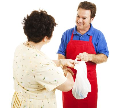 Friendly shop man hands a woman her purchases in a bag.  Isolated on white. Stock Photo - 6810148