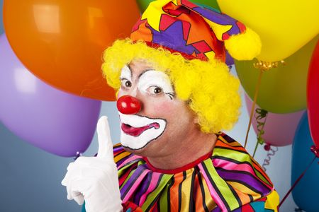 A colorful clown putting his finger to his lips so you will be quiet. Stock Photo - 6810170
