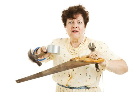 home repair: Older lady holding tools.  She is confused and overwhelmed by home improvement project.  Isolated on white.   Stock Photo