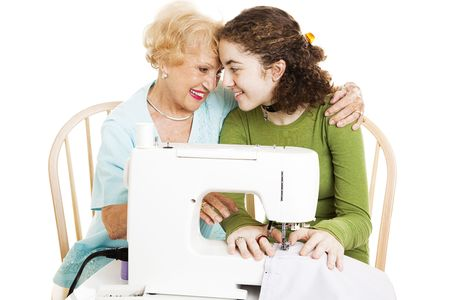 Grandmother teaches her teen granddaughter how to sew.  Isolated on white.   photo