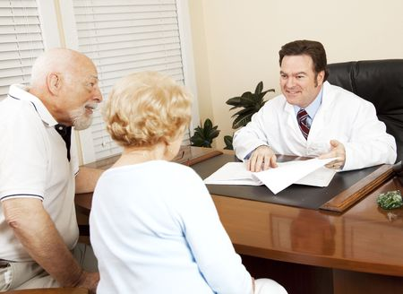 gives: Doctor reviews the medical test results of a senior couple and gives them the good news.