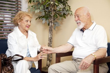 Senior husband and wife wait together and holding hands in the doctors waiting room.   photo