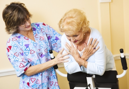 Senior woman using chiropractic Roman Chair to stretch her spine, with the help of a nurse.   Stock Photo