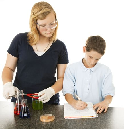 Older sister helping her little brother with his school science project.  Isolated on white.   photo