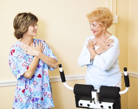 Senior woman at chiropractors office, working with a physical therapist to learn exercises for her back problems.   photo