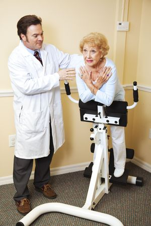 Chiropractic doctor helps elderly patient with her physical therapy.   photo