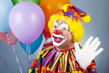 birthday clown: Happy clown with helium balloons, waving hello.