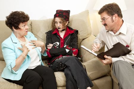 Mother explains herself to a family counselor while her rebellious teen daughter looks on.