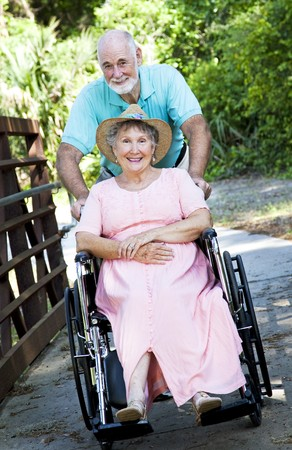 휠체어 공원에서 그의 비활성화 된 아내를 추진하는 수석 남자. 스톡 콘텐츠