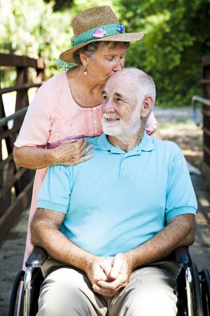 dementia: Senior woman caring for her disabled husband.