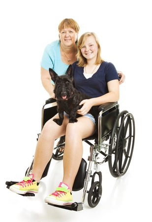 Disabled teen girl in wheelchair, posing with her mom and dog.  Full body isolated. photo