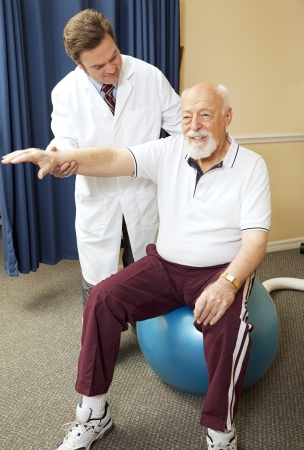physical: Chiropractor helping senior patient with physical therapy routine.