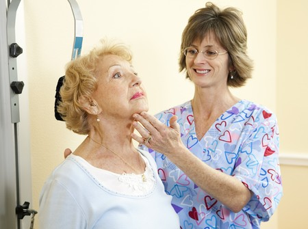 Physical therapist in chiropractors office helping a senior woman exercise her neck.  photo