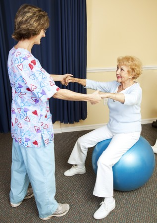 Physical therapist using pilates ball to work with senior chiropractic patient.   photo