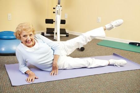 彼女のヨガのマットの上にストレッチ体操を行う幸せの年配の女性に合います。