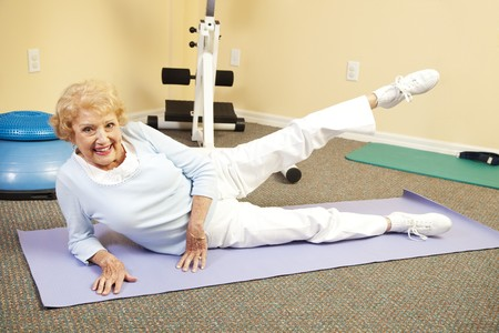 calisthenics: Fit happy senior woman doing stretching exercises on her yoga mat.