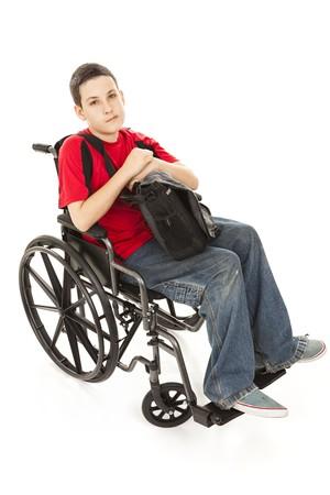 彼の車椅子で無効になっている十代の男の子の肖像画。 分離した完全なボディ。 真剣な表情。 写真素材