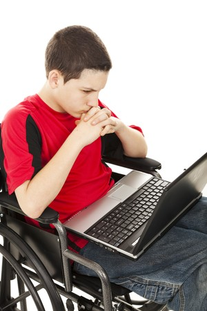 Teen boy in a wheelchair communicating via his laptop computer.  Isolated on white. photo
