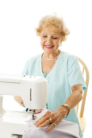 Retired senior lady enjoys sewing in her spare time.  Isolated on white. photo