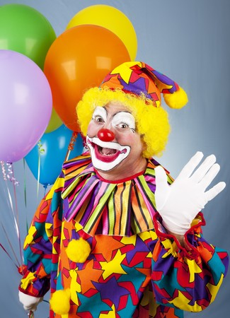 Friendly circus clown holding a bunch of balloons and waving hello. photo